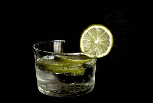tonic with lime fruits isolated in black background