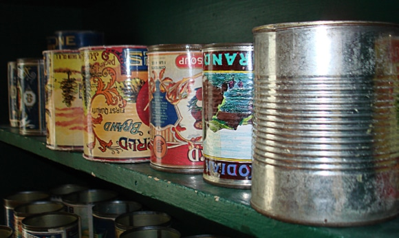 Some cans with very old labels cleaned out and on a shelf - they were upside down on purpose...