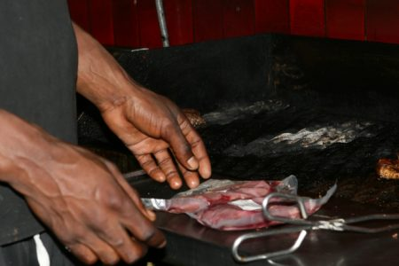 Restaurant bbq with meat being unwrapped on a flame grill
